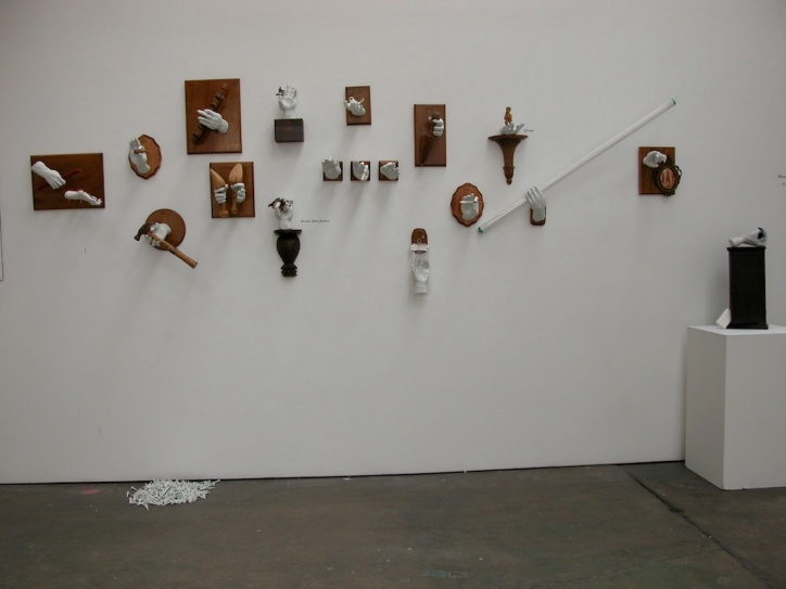 Installation view of contemporary ceramic figurative art, porcelain hands interacting with objects