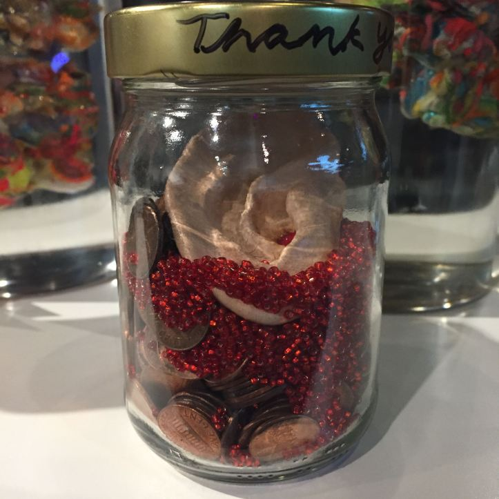 """Thank You for Your Support"" by Lee Puffer. Ceramic severed ear, glass beads, pennies and text in glass jar, 2014"